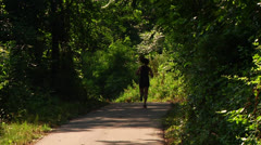 Unidentifiable girl jogging through the woods on a bike path Stock Footage