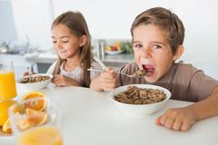 Stock Photo of Boy eating cereal next to his sister