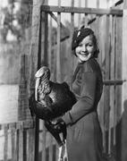 Portrait of smiling woman holding live turkey - stock photo