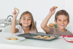 Siblings raising homemade cookies - stock photo