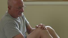 A senior main rubs his injured knee to sooth pain - stock footage