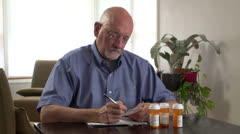 Senior man reviews his medical prescriptions, dolly - stock footage