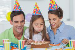 Little girl blowing out her candles - stock photo