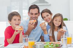 Family eating pizza slices - stock photo