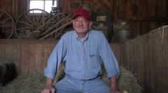 Farmer sitting on hay in a barn Stock Footage