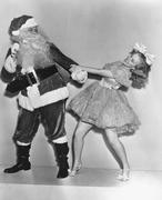 Woman trying to dance with Santa Claus - stock photo