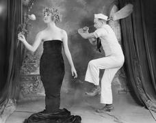Sailor hitting elegant woman with broom - stock photo