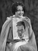 Woman with portrait of man on magazine cover - stock photo