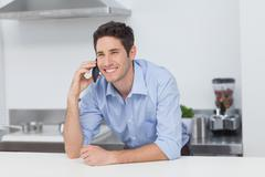 Man having a phone conversation in the kitchen Stock Photos
