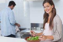Woman mixing a salad in the kitchen Stock Photos