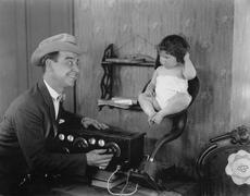 Father with baby in speaker horn of old radio Stock Photos