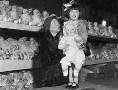 Mother and daughter with shelves of dolls Stock Photos