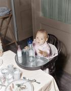 Baby in highchair with large and small bottles Stock Photos