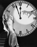 Woman with huge clock recoiling from frightening hand Stock Photos