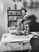 Woman arranging flowers at home Stock Photos