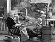 Elderly couple on porch of farmhouse Stock Photos
