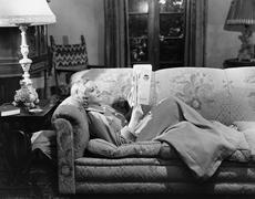 Woman reading on couch - stock photo