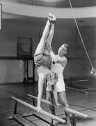 Coach helping woman on parallel bars Stock Photos