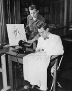 Young men using sewing machine - stock photo