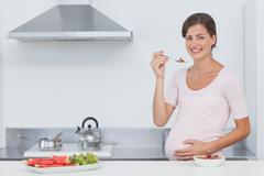 Pregnant woman eating cereal in the kitchen - stock photo