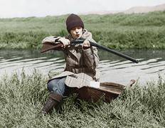 Female hunter with gun near river Stock Photos
