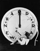 Woman with clock at midnight on New Years Eve - stock photo