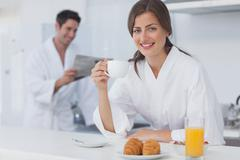 Stock Photo of Woman with a dressing gown having breakfast