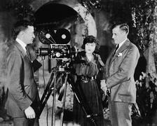 Three people with movie camera - stock photo