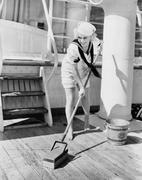 Female sailor swabbing boat deck - stock photo
