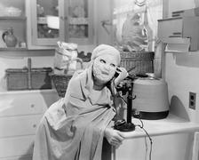 Woman wearing mask talking on phone - stock photo