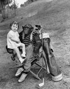 Monkey with golf clubs and toddler girl Stock Photos