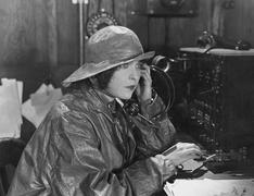 Woman in raincoat sending message in Morse code - stock photo