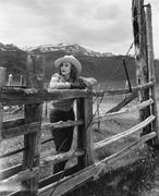 Woman leaning on wooden fence on ranch Stock Photos