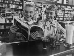 Girlfriends looking at magazine at soda fountain Stock Photos