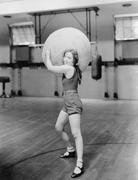 Woman in gymnasium with huge ball Stock Photos