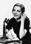 Stock Photo of Smiling woman using telephone