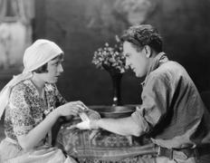 Woman bandaging mans hand Stock Photos