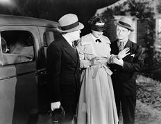 Men leading blindfolded woman - stock photo