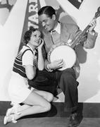 Mies pelaa banjo varten Adoring nainen Kuvituskuvat