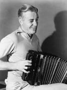 Winking man playing accordion - stock photo