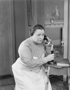 Worried woman using telephone - stock photo