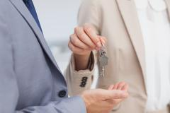 Real estate agent giving house key Stock Photos