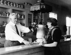 Stock Photo of Man serving beverage to woman at counter