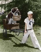 Girl in sailor suit pulling dog in basket Stock Photos