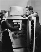 Couple with open refrigerator - stock photo