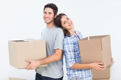 Wife and husband carrying boxes in their new house - stock photo