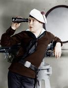 Portrait of sailor looking through binoculars - stock photo