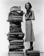 Woman with pile of large books - stock photo