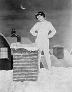 Young woman looking at chimney on snowy roof Stock Photos