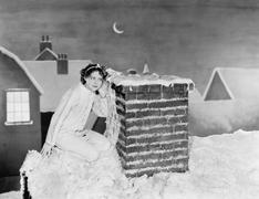 Young woman listening at chimney on snowy roof Stock Photos